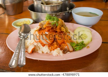 thai food - barbuced red pork and  crispy pork in sauce with rice serve with soup on blur background