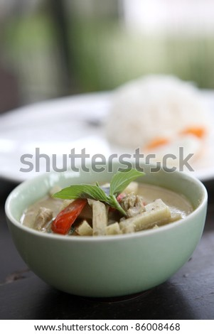 Thai food chicken green curry with rice in wood background - stock photo