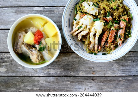 Thai Food : Chicken soup with potato and tomato, Sea Crab  stir fried  in Yellow Curry  with Coconut Milk and cellophane noodle on wooden table - stock photo