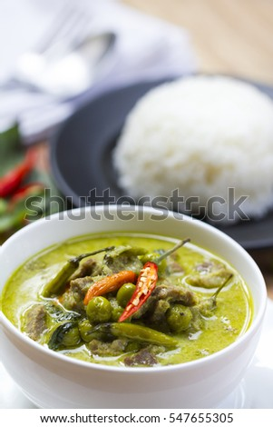 Thai Food: Green curry in round white bowl with steamed jasmine rice