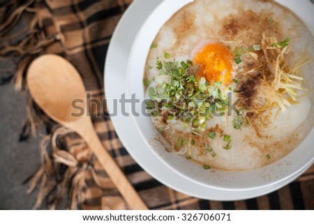 "Thai foods ""Joke"" (rice porridge) a rice soup cooked with pork broth with an egg in the middle and garnished with slices of ginger, spring onions and a dash of pepper."