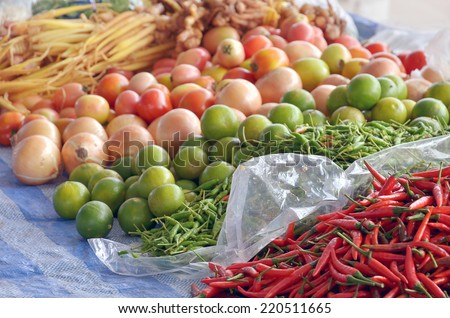 Thai fresh herb and spicy in Thai food market. Consist of red and green chilli, lime, tomato, onion, ginger and fingerroot/krachai. - stock photo