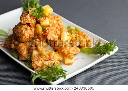 Thai fried calamari appetizer with fresh pineapple chunks. - stock photo
