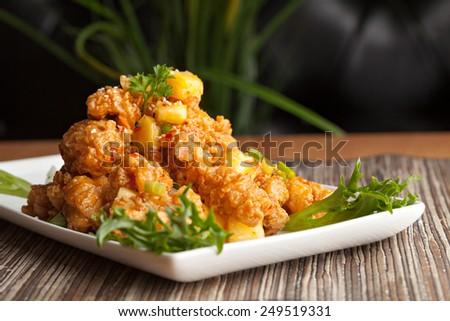 Thai fried calamari appetizer with fresh pineapple chunks - stock photo