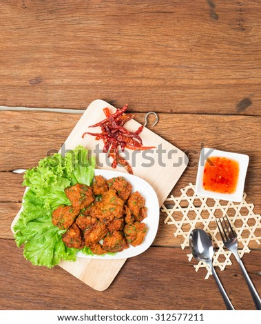Thai fried fish cake (Tod Mun Pla) or prawn fritter ball with dipping red sauce and spoon Thai food traditional recipe on wooden background  - stock photo