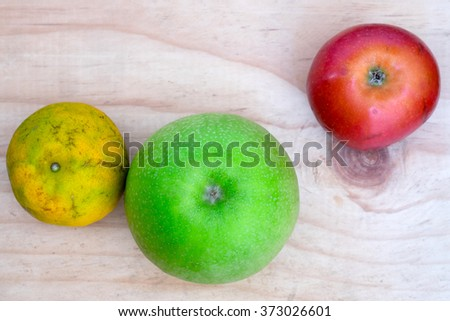 Thai fruits on wooden table - melon, red apple and Tangerine
