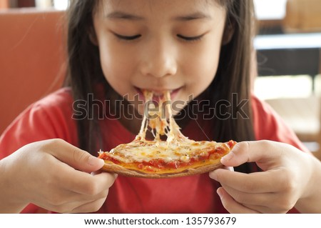 Thai girl enjoy eating pizza. - stock photo