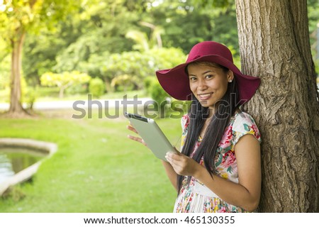 Thai girl using tablet in park
