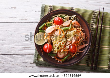 Thai green papaya salad with shrimp on a plate on the table. horizontal view from above - stock photo