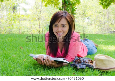 Thai happy woman reading book in park