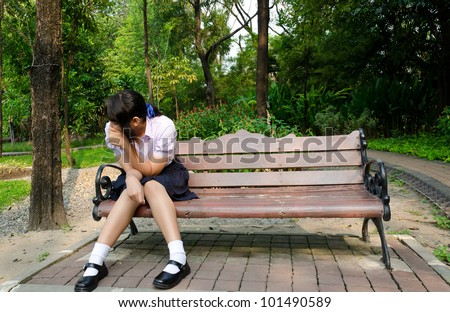 Thai high-school student crying alone on the bench in the park. - stock photo