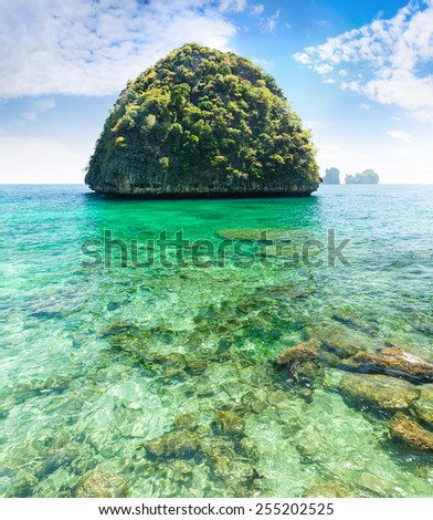 Thai island with transparent green water and blue sky  - stock photo