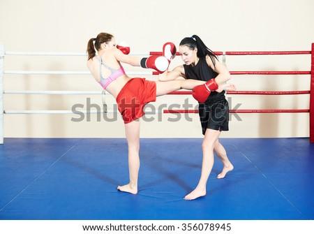 Thai kickboxing match. Muay thai female boxers fighting at training boxing ring - stock photo