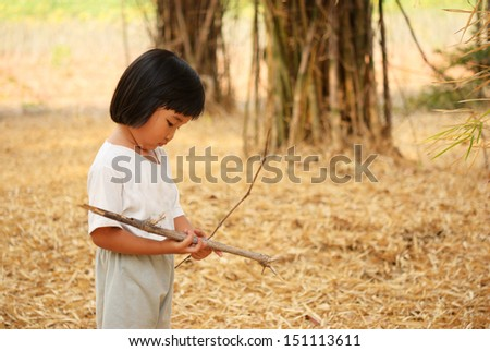 Thai kid learning about nature in bamboo garden - stock photo