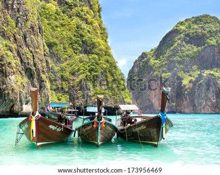 Thai long-tail boats in the turquoise waters of Maya Bay, Ko Phi Phi, Thailand. - stock photo