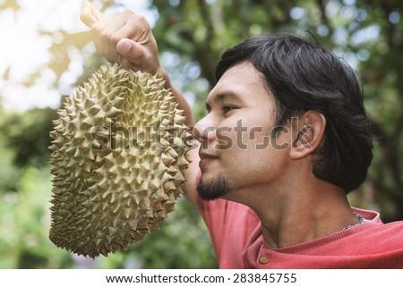 Thai man like smell of durian fruit - stock photo