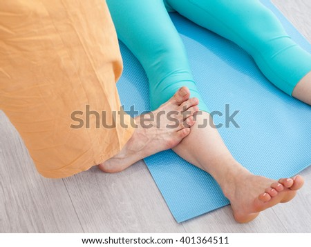 Thai massage session - man presses on woman's leg by the foot