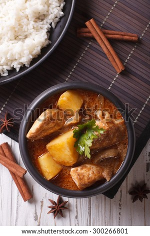 Thai massaman curry with chicken in a bowl and rice on the table close-up. vertical top view - stock photo