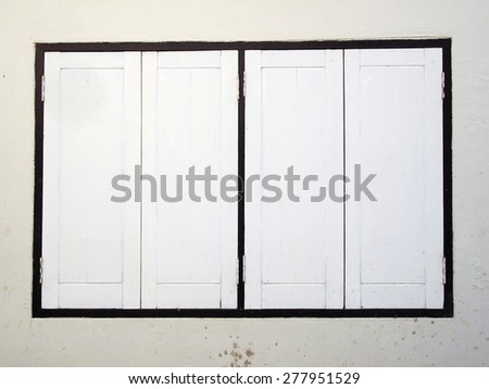 Thai old wooden door with white wall - stock photo