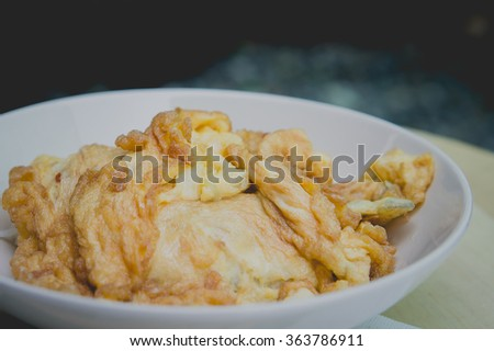 Thai omelette or scrambled eggs on the wood table.Omelette Tunterma.Tatar cuisine. close up. - stock photo