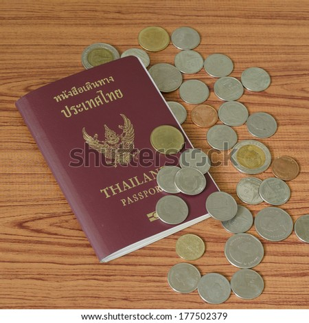 thai passport with coin on wood table background - stock photo
