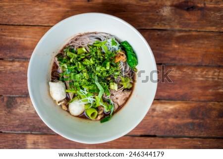 Thai pork noodle soup on wooden background - stock photo