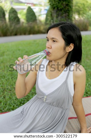 Thai pregnant mom was drinking water in the garden for good health.