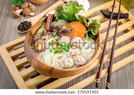 Thai ramen noodle on table with garnish and vegetables.
