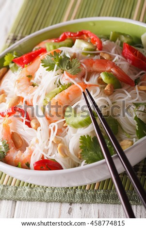 Thai salad with glass noodles, prawns and peanuts in a bowl close-up. vertical - stock photo