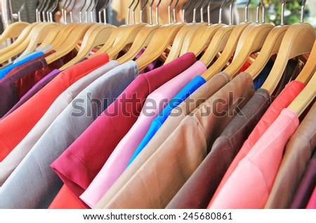 Thai silk clothes on hangers - stock photo