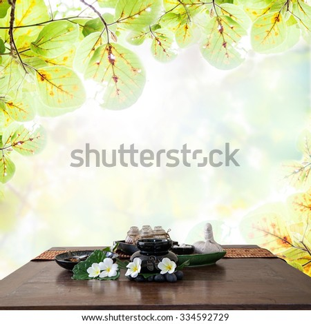 Thai spa massage setting  herbal compress balls, essential oil bottle,  frangipani and incense ,on table natural green background. - stock photo