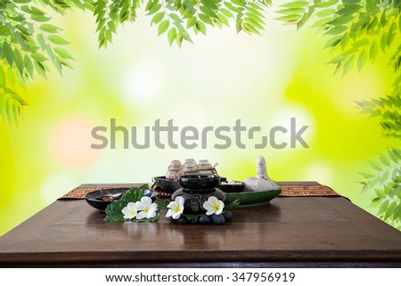 Thai spa massage setting  herbal compress balls, essential oil bottle,  frangipani and incense ,on table natural green background - stock photo
