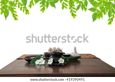 Thai spa massage setting herbal compress balls, essential oil bottle, frangipani and incense on green leaves background - stock photo