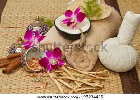 Thai spa massage setting , Massage oil, body scrub, Towels,Cinnamon sticks with orchids flower - stock photo