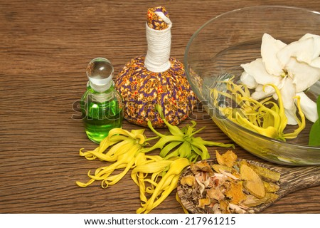 Thai spa massage setting with thai  herbal compress balls, essential oil bottle, towel,ylang-ylang flower in water - stock photo