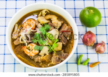 Thai spicy and sour soup (Tom yum) of shrimp, squid, pork leg and mushroom, top view - stock photo