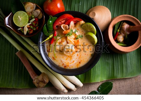 Thai spicy and sour soup with prawn (Tom Yum Goong) on banana leaf, popular Thai cuisine - stock photo
