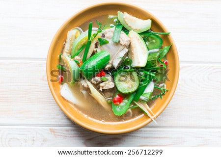 Thai Spicy Mixed Vegetable Soup with pork ribs on wood table - stock photo