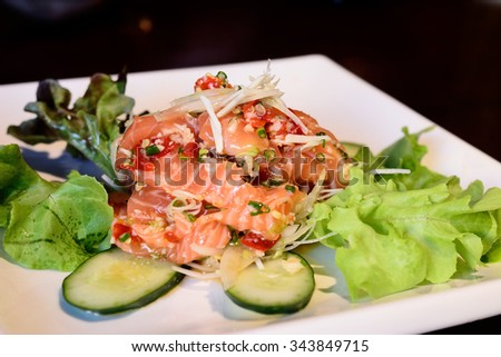 Thai spicy salmon salad , mixed vegetable and herb - stock photo