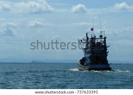 Thai squid fishing vessel from the South of Thailand heading out for fishing with blue sky background and white cloud.