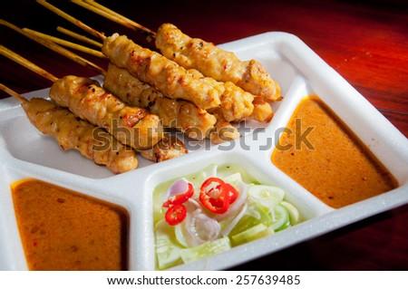 "Thai street food ""Moo Satay"" is marinade grilled pork serve with peanut sauce and salad in Styrofoam tray. - stock photo"