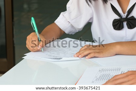 Thai students writing on a paper for exams and admissions in high school, Thailand  - stock photo