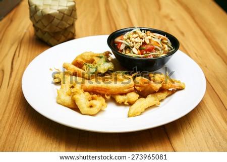 Thai style appetizer of fried tempura vegetable  with dipping sauce.Som Tam Thai - Thai Green Papaya Salad with peanuts. Papaya salad set on wood table. - stock photo