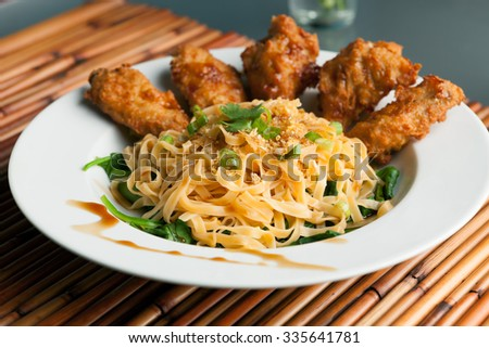 Thai Style Fried Chicken Wings On A Round White Plate With Egg Noodles And Spinach