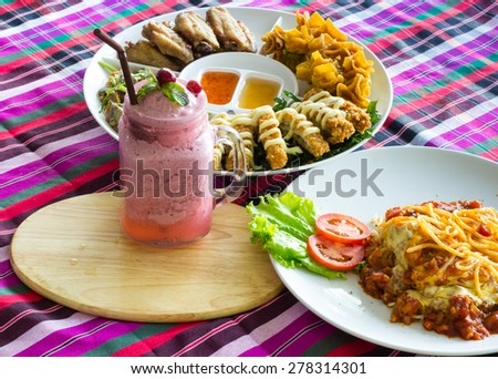 Thai-style Hors d'oeuvres and Blueberry smoothie and Spaghetti Bolognese on loincloth - stock photo