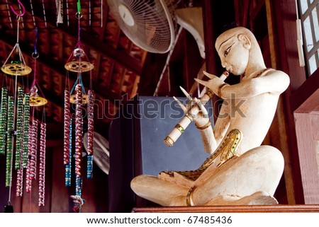 Thai style musician  wood sculpture is playing music, Rayong Thailand - stock photo