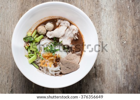 Thai style noodle,bowl of thai style beef noodle soup on wooden background, Boat Noodle , Moo nam tok. - stock photo