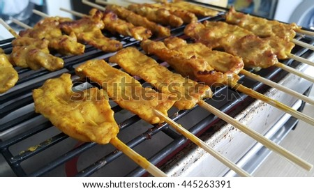 Thai style pork satay grilled on the electric barbecue. - stock photo