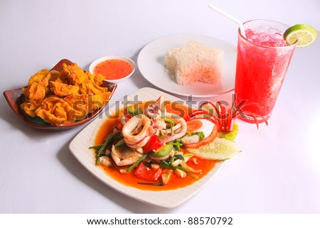 Thai style small meal contains steam rice, fried ravioli, Stir fried squid with salted egg yolk and red Cider-Soda, Sriracha Thailand - stock photo