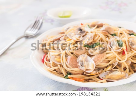 thai style spicy spaghetti with the clams on the white cloth table - stock photo